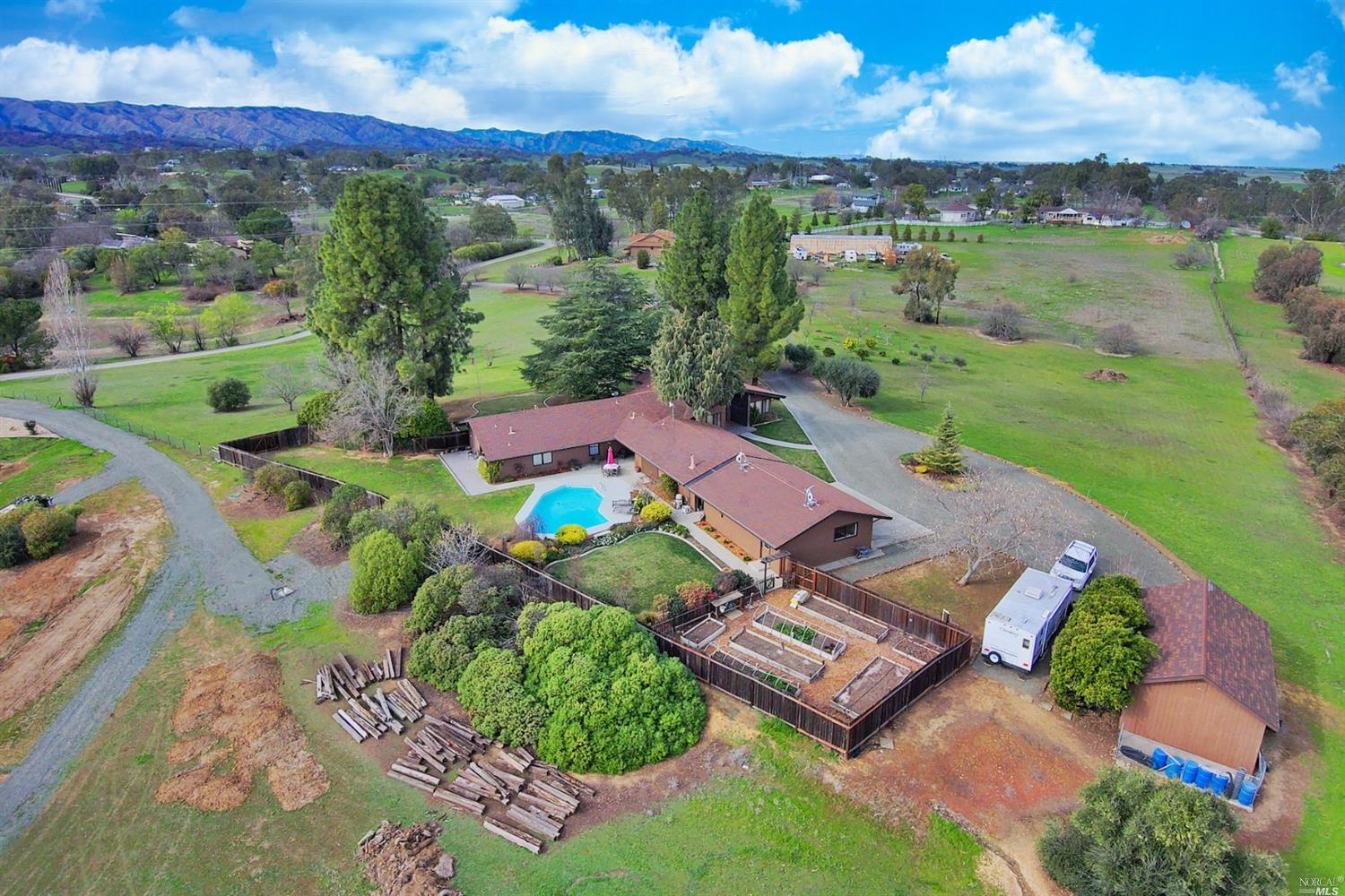 Coveted Vacaville country property with 5 usable acres showcasing a large custom single-story home, pool, 3-car garage, RV parking and workshop with wine cellar! Enter tree-lined driveway to enjoy panoramic views of the hills and orchard comprised of fruit, olive and nut trees. Rich land and fenced high-producing garden have private well irrigation. Entry welcomes with brick porch and double doors opening to the exposed wood beam vaulted ceilings and epic views through many large windows. Family/dining room with stone fireplace and sliding glass door. Kitchen with newly installed island cooktop, double oven, granite, backsplash, stainless steel appliances, pantry cabinetry and dining area. Den, ideal for home office and massive bonus room e