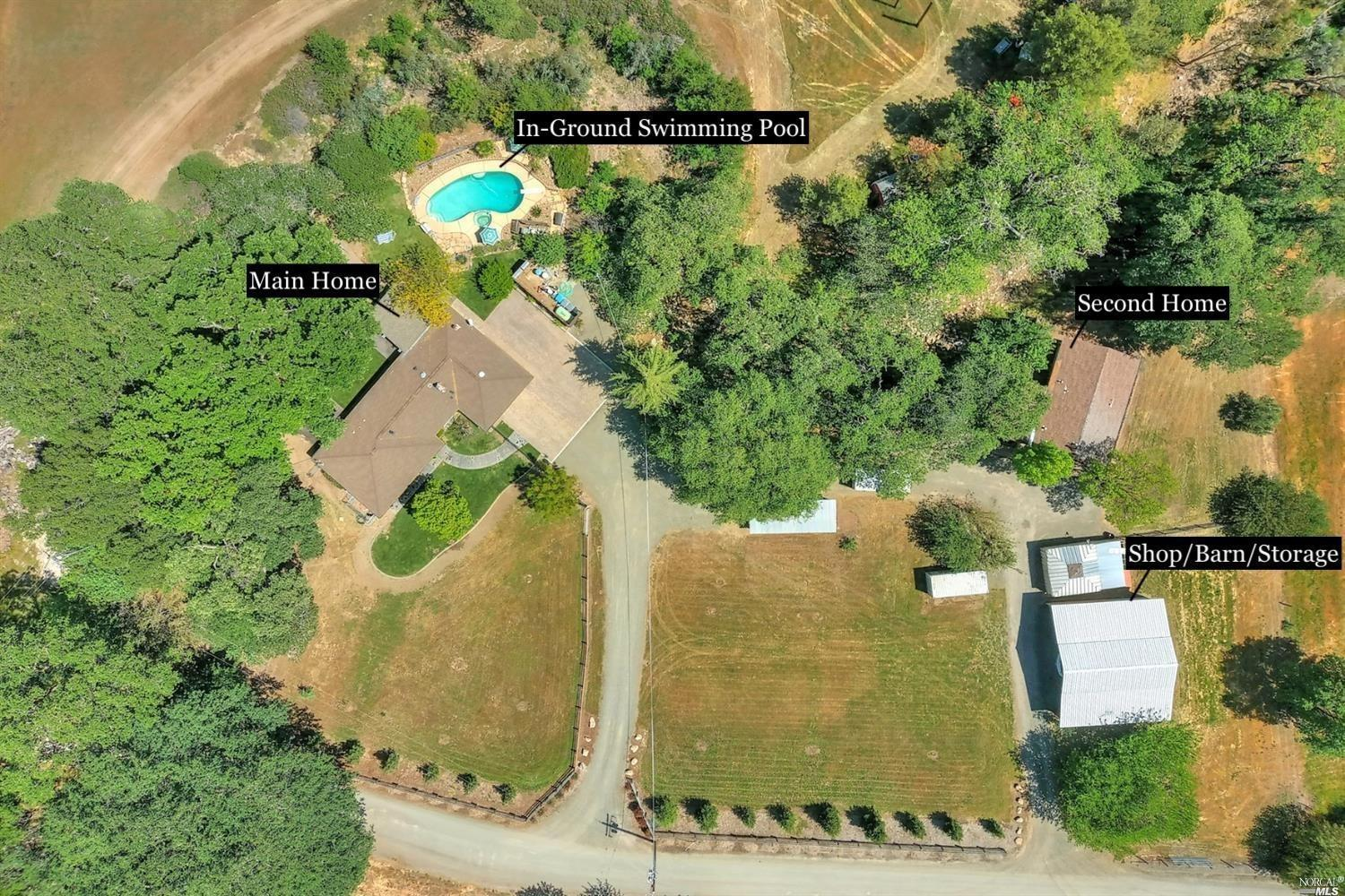 2 Homes On 10 Acres With Large Shop/Barn, Sparkling In-Ground Pool, RV Parking Plus Potential To Subdivide! The Main Home Features 3 Bedrooms, 2 Bathrooms With Updates Throughout Including A Beautiful Kitchen W/ Custom Hickory & Black Walnut Cabinetry, Copper Sink, Stainless Steel Appliances, Granite Countertops, Breakfast Counter, Updated Bathrooms W/ Tile Floors, Tile Surround Shower & Rain Showerheads, Recessed Lighting, Ceiling Fans, Updated Windows, Wood Burning Stove W/ Slate Surround, Travertine Entry & Recessed Lighting. 2nd Home Features 3 Bedrooms, 1 Bathroom, Granite Countertops & Separate Driveway Entrance. Property Highlights Include Paver Driveway, Expansive Stamped Concrete In Front & Backyard, In-Ground Swimming Pool W/ Divi