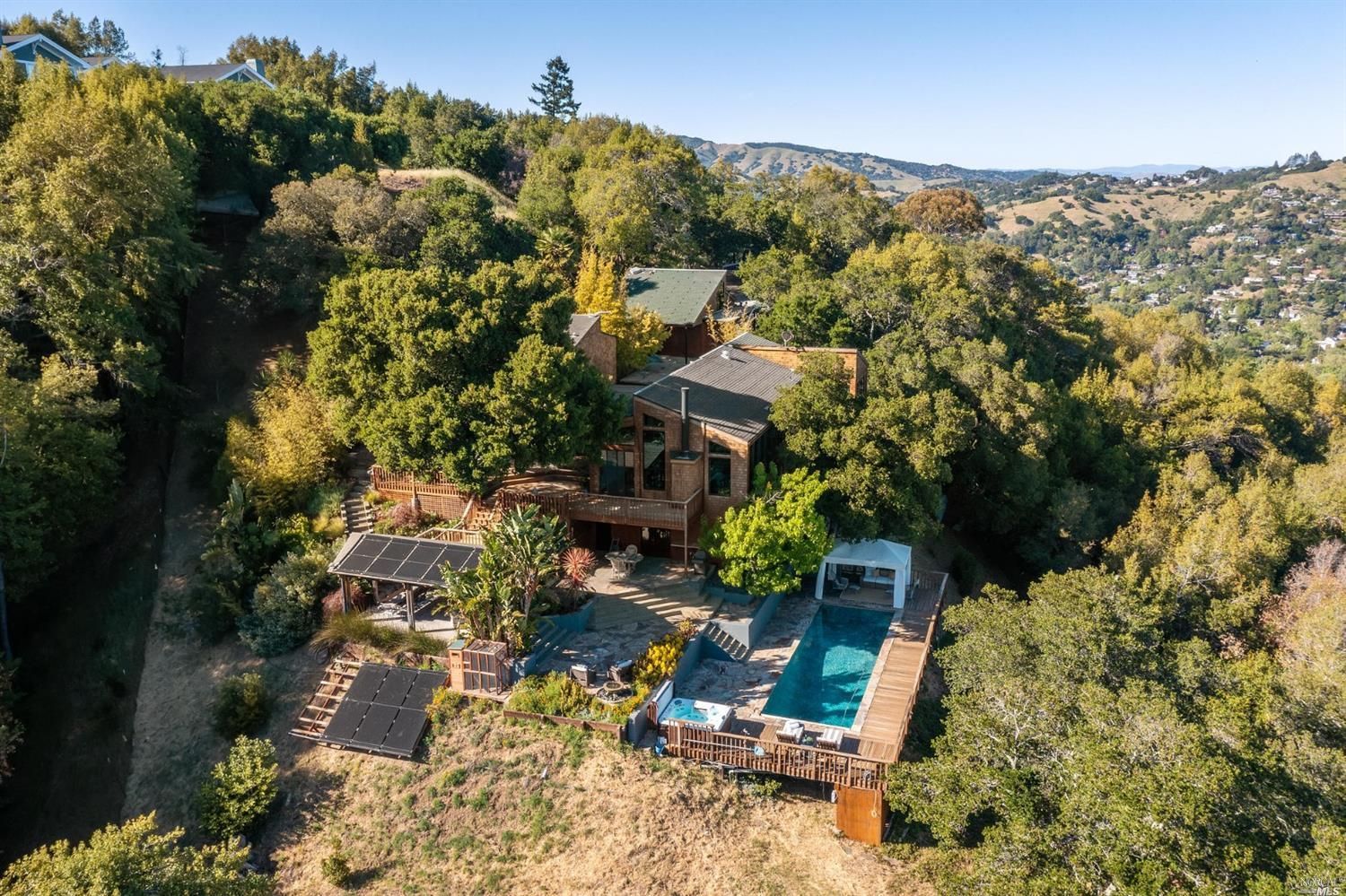 Rarely available, spectacular gated estate on almost an acre in San Anselmo. Featuring a sparkling pool & spa w/ panoramic views to the SF Bay & beyond. This amazing home features a private en-suite primary bedroom + spa like bath on the upper level. Main level: 2 bedrooms, formal dining room & living room complete w/ fireplace, high ceilings & breathtaking views. Thoughtfully designed chef's kitchen w/ Sub Zero fridge, opens to a family room w/fireplace + casual dining w/ treetop views. Lower level: 2 bedrooms + 2nd living room & full kitchen opening to the grounds & pool area. Enjoy entertaining w/ multiple deck & patio spaces: pergola overlooking the pool & views for al fresco dining. It's a magical, lushly landscaped setting. 2 garage, studio w/ half bath above, a fantastic home office. Easy access to world class hiking/biking trails. Highly regarded schools. Just a couple minutes to downtown SA, yet blissfully away from it all. This is the good life. Come home to San Anselmo.