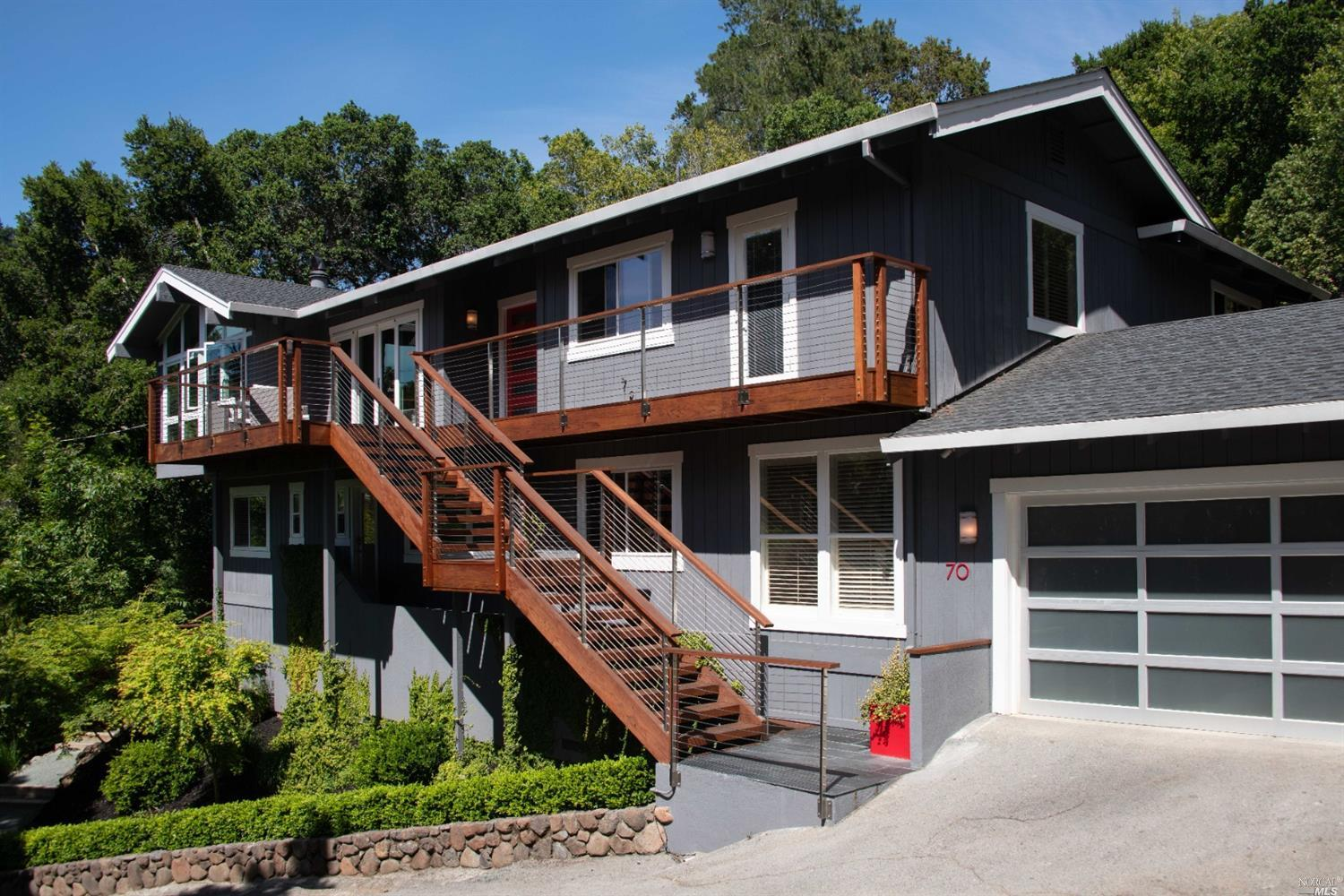 This remodeled home has a versatile floorplan w/ great flow and spacious living areas inside and out. On a private drive low in the hills, it's the perfect place to live & enjoy the best of Marin & the Bay Area, so close to shops, restaurants, outdoor rec' & commuter transportation! The main level consists of a formal entrance; a LR with a vaulted ceiling, a wall of windows & a fireplace; a formal DR; a modern, an open kitchen; a comfortable family room w/ fp; & a spacious primary bdrm suite with 2 walk-in closets. The lower level consists of 2 large bdrms, a hall bath, a laundry room with storage, and a spacious, versatile, 4th bdrm suite that has a kitchenette, its own washer/dryer + a separate entrance. There are redwood decks off the front & back of the house. The property is landscaped with mature trees, foliage & pathways, a hot tub, a raised vegetable garden + places for play. Attached, 2 car garage + 4 private pkng spaces. Kentfield Schools.