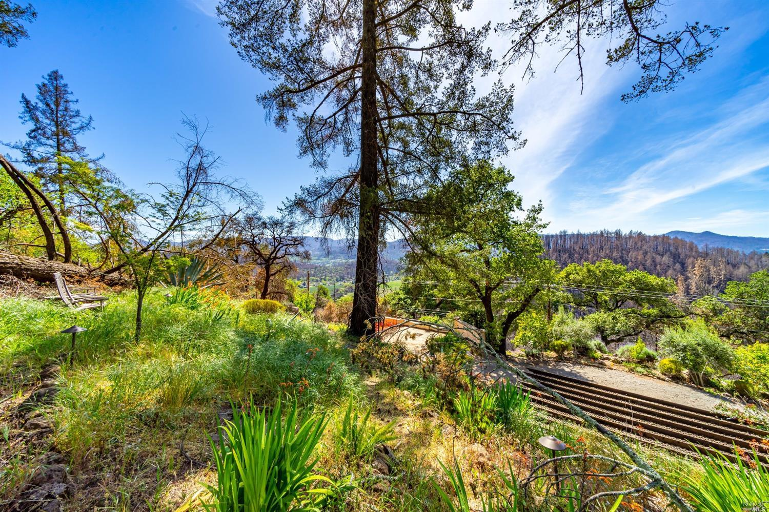 This unique view land offering is suitable for a luxury home close to town. The Northwest facing views take in magnificent sunsets, glimmering valley lights, and the distant mountains. The residential parcel offers 0.97+/- acre of prime buildable land and is moments from Downtown St Helena. When visiting, one would immediately notice the sense of privacy, elevation, and sprawling tiers of native landscape. The location grants a country feel down private lane. Bedrock and stone elements mixed with backdrops of mature trees make this a true rare find. Buyer to confirm utilities that may be available for use onsite.